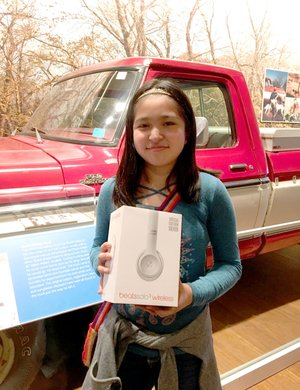 Photo submitted Ruby Vega, seventh-grade student at Siloam Springs Middle School, was one of five students to win The Walmart Museum's national essay contest celebrating Sam Walton's 100th Birthday. She is pictured in front of Walton's truck in the museum with her prize, a pair of special Spark Edition Beats by Dre' headphones.