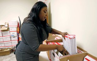 FILE- In this Feb. 15, 2018, file photo, Angela Thames, office manager of a north Jackson, Miss., Liberty Tax Service, organizes tax returns. Thames says each completed tax return is carefully separated and filed for quick retrieval if needed. The tax deadline does typically fall on April 15 but that's a Sunday this year and Monday is Emancipation Day, a Washington D.C. holiday. That means that taxpayers nationwide get a little breathing room and have until Tuesday, April 17, to get the job done. (AP Photo/Rogelio V. Solis, File)