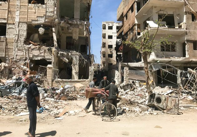 people-stand-in-front-of-damaged-buildings-in-the-town-of-douma-the-site-of-a-suspected-chemical-weapons-attack-near-damascus-syria-on-monday-april-16-2018