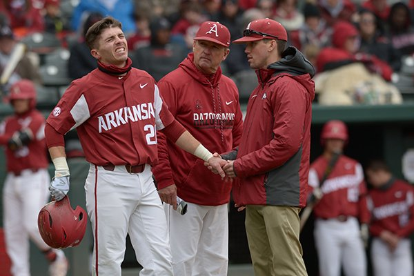 Dave Van Horn checks on Carson Shaddy (20) after he was hit in the hand by a pitch during a game with South Carolina in Fayetteville, April 14, 2018.