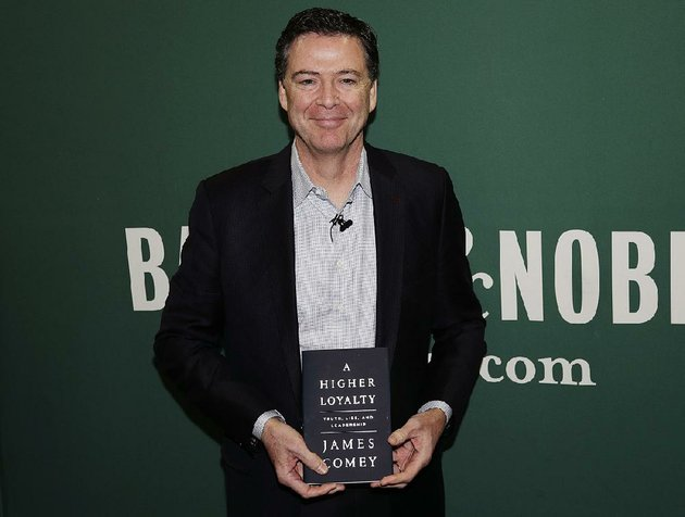 former-fbi-director-james-comey-poses-with-his-new-book-during-an-appearance-wednesday-at-a-barnes-noble-in-new-york
