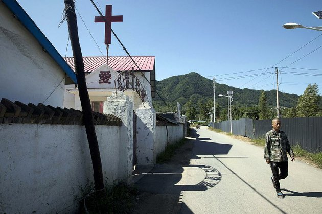 a-man-walks-past-a-church-in-the-chinese-border-town-of-jian-in-northeastern-chinas-jilin-province