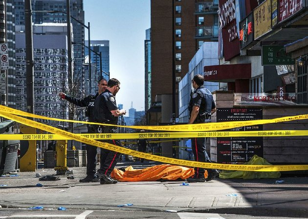 police-officers-stand-by-a-covered-body-monday-in-toronto-after-a-van-drove-onto-a-sidewalk-and-crashed-into-a-crowd-of-pedestrians