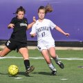 Bentonville's Anna Passmore (left) kicks the ball in front of Fayetteville's Bella Kicklak on Monday...