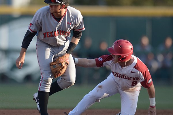 Arkansas outfielder Eric Cole slides into second base while Texas Tech shortstop Michael Davis covers during a game Tuesday, April 24, 2018, in Fayetteville.