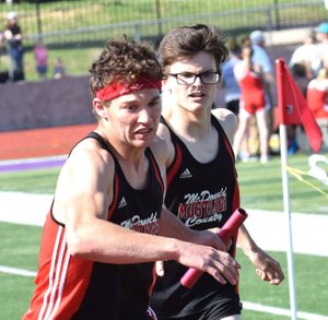 RICK PECK/SPECIAL TO MCDONALD COUNTY PRESS Cole DelosSantos takes a handoff from John Howard during the McDonald County Mustangs' 4x800 relay team's second-place effort at the Monett Relays held on April 24 at Monett High School.