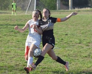 RICK PECK/SPECIAL TO MCDONALD COUNTY PRESS McDonald County's Ava Smith (left) battles a Neosho defender for control of the ball during the Lady Mustangs' 3-0 loss on Monday night at McDonald County High School.
