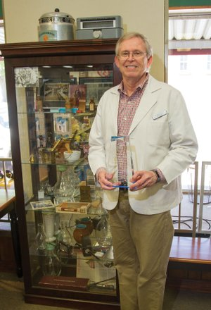 Rick Pennington of Lonoke stands next to a display of pharmacy collectibles while holding his award for being named the Lonoke Area Chamber of Commerce Citizen of the Year. Pennington has been a pharmacist at Lyons Drug Store for close to 44 years, and purchased the store 13 years ago.
