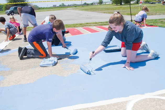 harding-academy-students-jack-thomas-and-sabrina-rampey-along-with-brylee-jeffrey-behind-thomas-paint-the-inside-of-the-3-point-line-on-an-outdoor-court-at-the-searcy-event-center