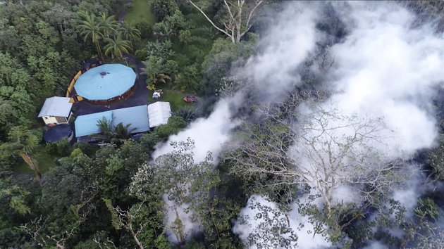 in-this-still-frame-taken-from-video-lava-flows-toward-a-home-in-the-puna-district-as-a-result-of-the-eruption-from-kilauea-volcano-on-hawaiis-big-island-friday-may-4-2018-the-eruption-sent-molten-lava-through-forests-and-bubbling-up-from-paved-streets-and-forced-the-evacuation-of-about-1500-people-who-were-still-out-of-their-homes-friday-after-thursdays-eruption-byron-matthews-via-ap