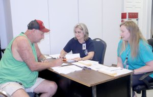 LYNN KUTTER ENTERPRISE-LEADER Jackie Apple of Lincoln signs up to receive fresh produce through farmers' markets in the area with Lisa McClelland and Casey Pruitt, both representatives with Area Agency on Aging of Northwest Arkansas.