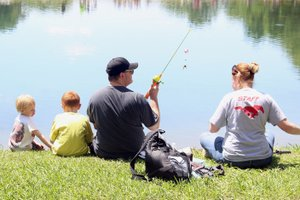 MEGAN DAVIS MCDONALD COUNTY PRESS/Southwest City's fishing derby is a family affair, as made evident by these parents last year, who loaded the bait, and their children, who cast the lines.