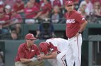 Arkansas trainer Corey Wood, left, tends to shortstop Jax Biggers, middle, while Razorbacks coach Dave Van Horn looks toward the dugout during a game against Texas A&M on Friday, May 11, 2018, in Fayetteville.