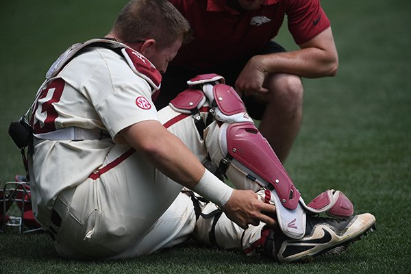 Arkansas catcher Grant Koch reaches for his ankle during the seventh inning of a game against Texas A&M on Sunday, May 13, 2018, in Fayetteville.
