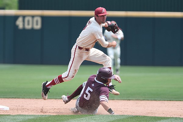 Jack Kenley watches his throw to first base after tagging Texas A&M's Logan Foster at second Sunday May 13, 2018 at Baum Stadium in Fayetteville. Arkansas won 6-3 to sweep the three game series.