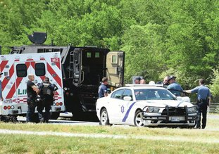 The Sentinel-Record/Grace Brown SUSPECT IN CUSTODY: Officers with Arkansas State Police and LifeNet personnel place Davy Wayne Rollins, 46, center, wearing a protective suit, into a patrol unit after he surrendered following a more than 10-hour standoff at the Combs Mobile Home Park, Unit 15, at 1780 E. Grand Ave., on Sunday