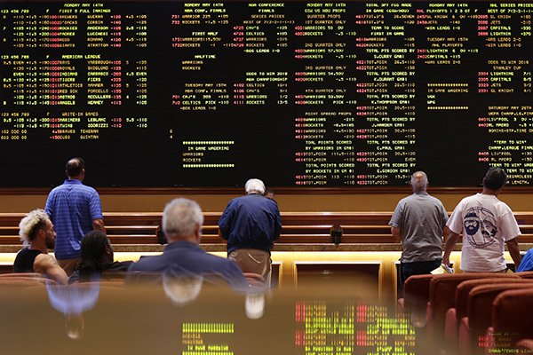 People line up to place bets in the sports book at the South Point hotel-casino, Monday, May 14, 2018, in Las Vegas. The Supreme Court on Monday gave its go-ahead for states to allow gambling on sports across the nation, striking down a federal law that barred betting on football, basketball, baseball and other sports in most states. (AP Photo/John Locher)
