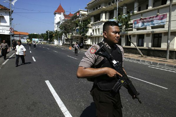 Credit AP  ACHMAD IBRAHIM					An officer stands guard on a road leading to the local police headquarters after an attack Monday in Surabaya Indonesia