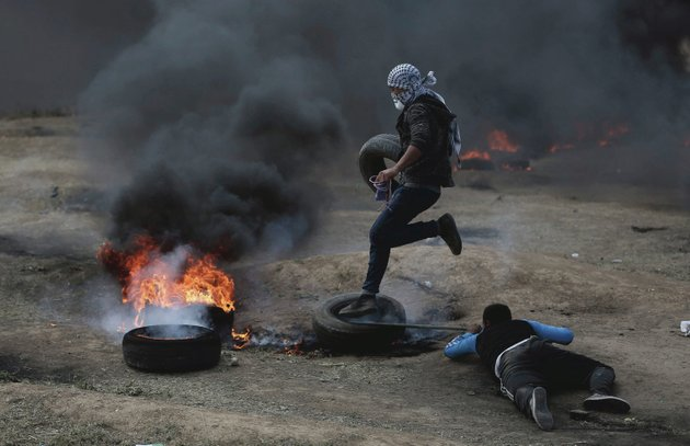 palestinian-protesters-burn-tires-during-a-protest-on-the-gaza-strips-border-with-israel-monday-may-14-2018-thousands-of-palestinians-are-protesting-near-gazas-border-with-israel-as-israel-prepared-for-the-festive-inauguration-of-a-new-us-embassy-in-contested-jerusalem-ap-photokhalil-hamra