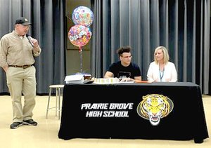 Submitted photo Prairie Grove senior Anthony Johnson (center) signs a national letter of intent to play college football for Hendrix College, of Conway, on Monday, April 23. Johnson was accompanied by his mother, Andrea Harrell (right) and Prairie Grove head football coach Danny Abshier. Johnson earned All-State and All-Conference honors leading the Tigers in rushing as a senior.