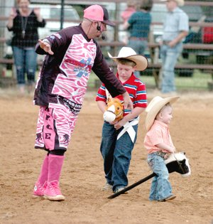 """MARK HUMPHREY ENTERPRISE-LEADER Jerry Casey, also known as """"The Sarge,"""" rodeo clown for the 64th annual Lincoln Rodeo in 2017 directs traffic during the stick-horse grand entry. Ethan Parker, 2017 Lincoln Riding Club Lil' Mister, was about to have a runaway with his stick-horse mount and had to be cautioned not to run over a little cowboy bringing up the rear of the grand entry. The 65th annual Lincoln Rodeo has been rescheduled for Aug. 9-11, 2018."""