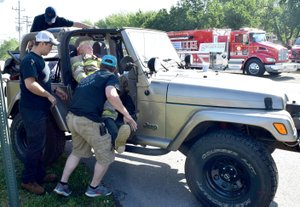 Westside Eagle Observer/MIKE ECKELS How many Decatur firefighters does it take to load a dummy into a jeep? Apparently, three, although two more joined in a short time later. The dummy, Decatur Fire Department's emergency response human analog, made the round trip ride to raise funds for the Arkansas Children's Hospital May 5.