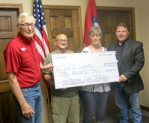 Westside Eagle Obsever/SUSAN HOLLAND John Mitchael (left), Gravette Historical Museum commission member, accepts a check for $50,000 from Bo Roberts and Wilma Fladager, representatives of Care and Share, at the May committee of the whole meeting. Mayor Kurt Maddox represents the city of Gravette in accepting the Care and Share donation, which is to be used for the museum commission's renovation of the old home economics building.