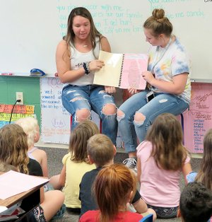 Westside Eagle Observer/RANDY MOLL Madi Boyd (left) and AnnDee Holt read a book they wrote to first-grade students at Gentry Primary School on Friday. Pre-AP English II students from Gentry High School wrote children's books for their end-of-the-year project and then read them to first-grade classes at the primary school.