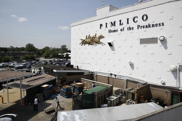 people-walk-outside-of-a-building-at-pimlico-race-course-as-preparations-take-place-for-the-preakness-stakes-horse-race-tuesday-may-15-2018-in-baltimore-pimlico-race-course-is-getting-all-gussied-up-again-this-week-ready-to-host-the-preakness-on-a-day-that-will-enable-the-148-year-old-track-to-survive-another-year-ap-photopatrick-semansky
