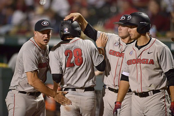 Georgia players congratulate Tucker Bradley (28), Georgia right fielder, after he scored a run Friday, April 14, 2017, during the ninth inning against Arkansas at Baum Stadium in Fayetteville.