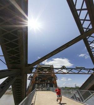 Arkansas Democrat-Gazette/JOHN SYKES JR. -  A jogger crosses the Clinton Presidential Park Bridge in Little Rock Wednesday, May 16, braving warm temperatures that reached into the 90s in central Arkansas.