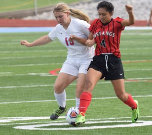 RICK PECK/SPECIAL TO MCDONALD COUNTY PRESS McDonald County's Karen Gasca (4) and Webb City's McKenzie Brown fight for control of a loose ball during the Lady Cardinals' 7-0 win on Monday night in the district soccer tournament at Webb City High School.