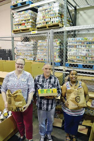 Melissa Allen, from left, community-programs director for the Community Action Program for Central Arkansas in Conway; Walter Callahan, volunteer; and Myracle White, pantry coordinator, hold some of the record 31,340 pounds of food collected by Conway, Mayflower and Vilonia residents through the 26th annual Letter Carriers' Stamp Out Hunger Food Drive.