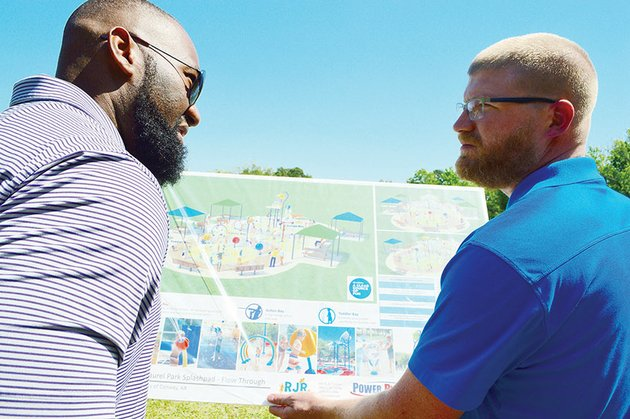 leo-cummings-iii-left-director-of-member-engagement-for-the-conway-area-chamber-of-commerce-and-derek-cox-assistant-director-of-conway-parks-and-recreation-look-at-the-plans-for-the-citys-first-splash-pad-during-a-groundbreaking-for-the-project-may-11-in-laurel-park-the-5485-square-foot-splash-pad-is-scheduled-to-be-open-july-4-mayor-bart-castleberry-said