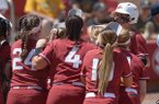 Arkansas players greet infielder A.J. Belans at home plate after Belans hit a solo home run in the fifth inning of a NCAA regional game against Wichita State on Saturday, May 19, 2018, in Fayetteville.
