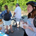 Emily Voight stops for a cup of coffee and a pastry Friday at the Bike NWA Energizer Station set up ...