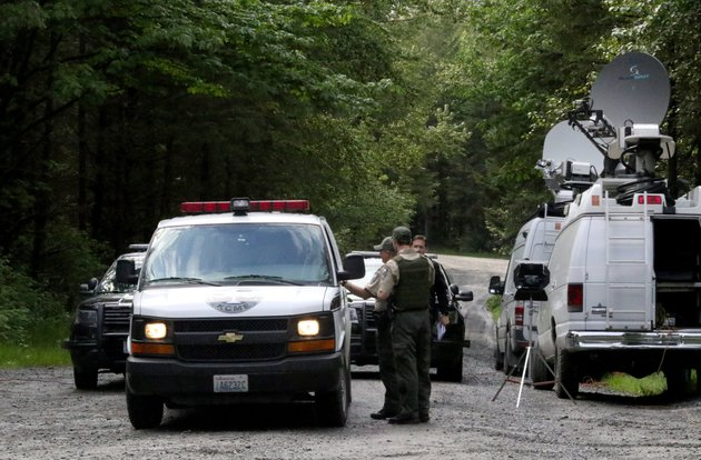 washington-state-fish-and-wildlife-police-confer-with-an-individual-from-the-king-county-medical-examiners-office-on-a-remote-gravel-road-above-snoqualmie-wash-following-a-fatal-cougar-attack-saturday-may-19-2018-one-man-was-killed-and-another-seriously-injured-when-they-encountered-a-cougar-saturday-while-mountain-biking-in-washington-state-officials-said-alan-bernerthe-seattle-times-via-ap