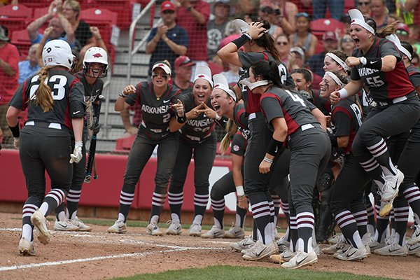 The Arkansas squad meets Hannah McEwen at home plate after her homer in the fourth inning against Wichita State Sunday May 20, 2018 during the NCAA Regional Softball Tournament at Bogle Park in Fayetteville. Arkansas won 6-4.