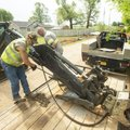 Jack Hutcheson (left) and Shawn Alley with the Benton County Road Department swap a bucket for a com...