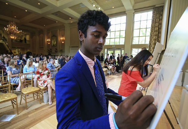 little-rock-central-high-school-students-anil-chakka-left-and-julianne-chung-sign-their-names-monday-during-an-event-to-celebrate-college-bound-little-rock-school-district-seniors-at-the-governors-mansion-chakka-plans-to-attend-vanderbilt-university-and-chung-plans-to-attend-rhodes-college