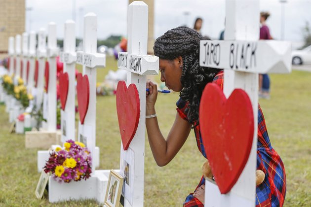 santa-fe-high-school-freshman-jai-gillard-writes-messages-on-each-of-the-10-crosses-in-front-the-school-monday-may-21-2018-in-santa-fe-gillard-was-in-the-art-class-friday-morning-knew-all-of-the-victims-of-the-shooting-texas-governor-greg-abbott-has-called-for-a-moment-of-silence-at-10-am-and-came-to-the-school-to-participate-steve-gonzaleshouston-chronicle-via-ap