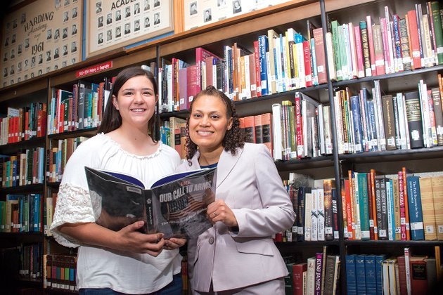 harding-academy-freshman-carson-mcfatridge-left-and-harding-academy-social-studies-teacher-angela-adams-look-at-the-life-magzine-book-our-call-to-arms-the-attack-on-pearl-harbor-in-the-school-library-mcfatridge-and-adams-have-been-invited-to-participate-in-educational-programs-this-summer-at-the-national-wwii-museum-in-new-orleans