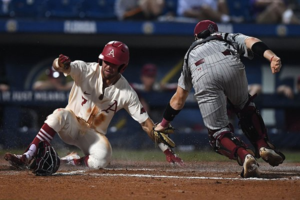 Arkansas' Jack Kenley scores ahead of the tag by South Carolina catcher Hunter Taylor during a game Wednesday, May 23, 2018, at the SEC Tournament in Hoover, Ala.