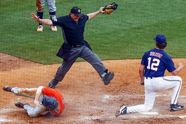 Auburn's Luke Jarvis (9) beats the tag from Mississippi pitcher Greer Holston (12) as he slides into home plate on a wild pitch during the seventh inning of a Southeastern Conference Tournament NCAA college baseball game, Wednesday, May 23, 2018, in Hoover, Ala. (AP Photo/Butch Dill)
