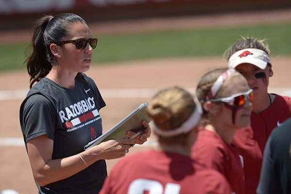 Arkansas coach Courtney Deifel prepares to step into the team huddle against Wichita State Saturday, May 19, 2018, at Bogle Park during the NCAA Fayetteville Softball Regional on the university campus in Fayetteville.