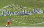 A young fan throws the ball under a tournament logo in the outfield during a rain delay in the seventh inning of a Southeastern Conference Tournament NCAA college baseball game between Georgia and Mississippi, Thursday, May 24, 2018, in Hoover, Ala. (AP Photo/Butch Dill)