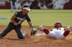 Oklahoma's Nicole Mendes (11) slides into second as Arkansas' Haydi Bugarin (10) tries to place the tag in the second inning during the first game of an NCAA softball super regional in Norman, Okla., Friday, May 25, 2018. (Sarah Phipps/The Oklahoman via AP)