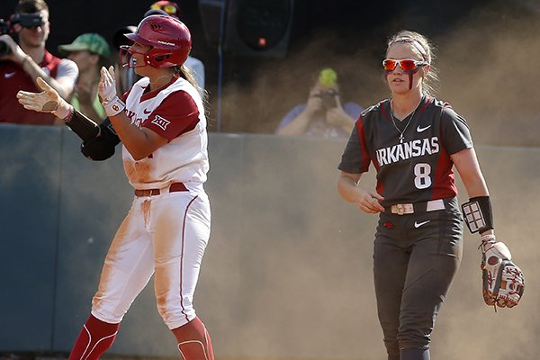 Oklahoma's Nicole Mendes, left, celebrates next to Arkansas' Autumn Buczek (8) during the fifth inning during the first game of an NCAA softball super regional in Norman, Okla., Friday, May 25, 2018. (Sarah Phipps/The Oklahoman via AP)