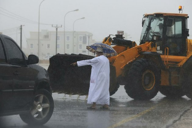 an-oman-official-directs-a-loader-driver-friday-to-tear-away-a-median-to-drain-a-flooded-street-in-salalah-after-cyclone-mekunus-heavy-rains