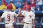 Arkansas shortstop Jax Biggers (9) greets first baseman Jared Gates (3) after Gates hit a home run during an SEC Tournament game against LSU on Saturday, May 26, 2018, in Hoover, Ala.